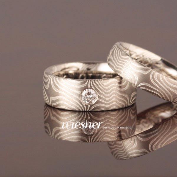 Bagassa Trauringe in Mokume Gane Technik mit einem großen Diamanten