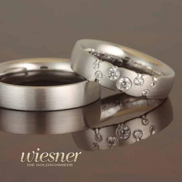 Trauringe Gerstner in Weißgold mit Diamanten gefasst im Damenring