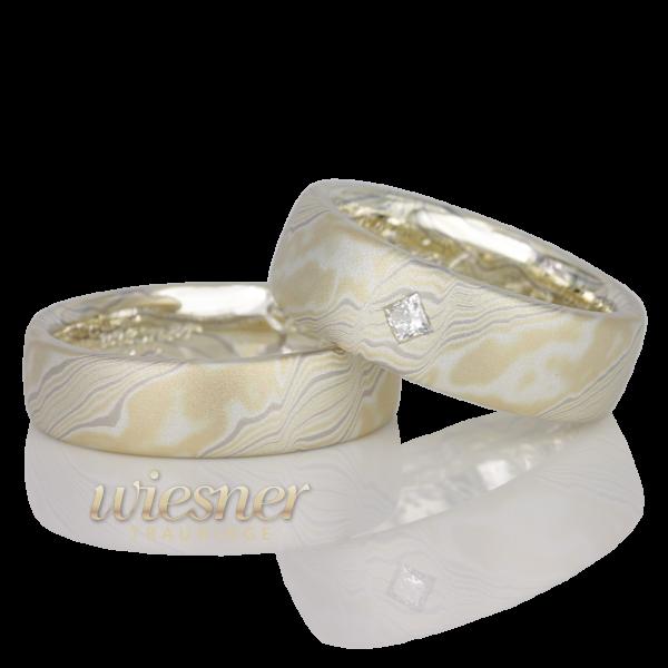 Mokume Gane Trauringe Bubunga in Gelbgold, Palladium und Silber mit Princess Cut Diamant